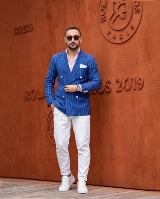 Cómo combinar: blazer cruzado de rayas verticales azul, camisa de manga larga rosada, pantalón chino blanco, tenis de cuero blancos