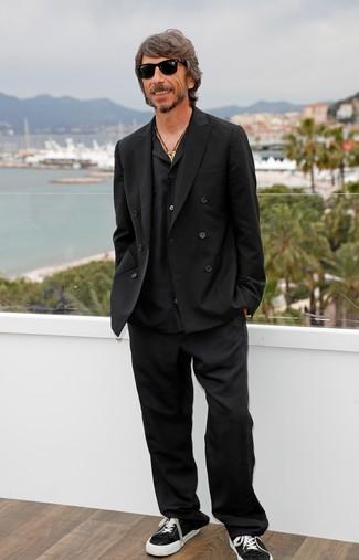 Cómo combinar: blazer cruzado negro, camisa de manga larga negra, pantalón de vestir negro, tenis de lona en negro y blanco
