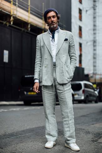 Cómo combinar: blazer cruzado de lino gris, camisa de manga larga blanca, pantalón de vestir de lino gris, tenis de cuero blancos