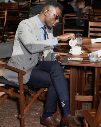 Cómo combinar: blazer cruzado gris, camisa de vestir celeste, pantalón de vestir azul marino, zapatos brogue de cuero marrónes