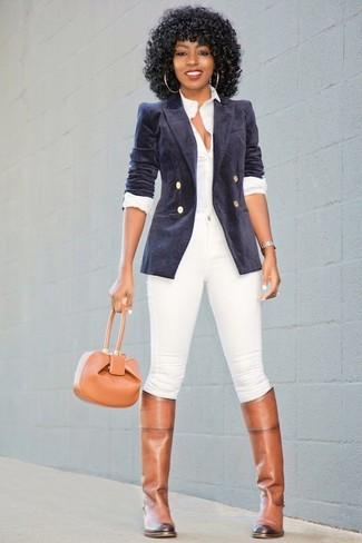 Cómo combinar: blazer cruzado de terciopelo azul marino, camisa de vestir blanca, vaqueros pitillo blancos, botas de caña alta de cuero marrónes