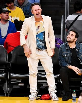 Cómo combinar: blazer cruzado en beige, camiseta con cuello circular estampada en multicolor, vaqueros en beige, tenis de lona estampados blancos