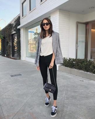 Cómo combinar: blazer cruzado de tartán gris, camiseta sin manga en beige, vaqueros pitillo negros, tenis de lona en negro y blanco