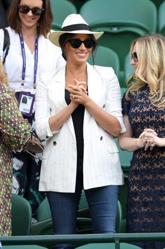 Look de Meghan Markle: Blazer cruzado de rayas verticales blanco, Camiseta sin manga negra, Vaqueros pitillo azul marino, Sombrero de paja en beige