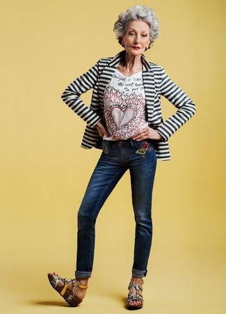 Cómo combinar: blazer de rayas horizontales en blanco y negro, camiseta con cuello circular bordada blanca, vaqueros bordados azul marino, sandalias con cuña de cuero con print de serpiente grises