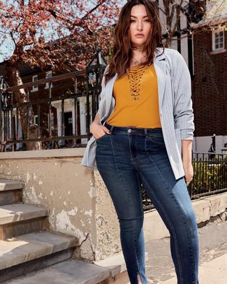 Cómo combinar: blazer de rayas verticales gris, camiseta con cuello en v mostaza, vaqueros pitillo azul marino, gargantilla dorada