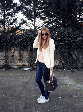 Cómo combinar: blazer blanco, jersey con cuello circular rosado, vaqueros pitillo azul marino, tenis de lona blancos
