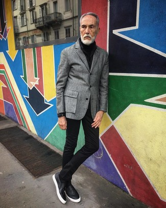Cómo combinar: blazer de lana gris, jersey de cuello alto negro, vaqueros pitillo negros, zapatillas slip-on de cuero negras