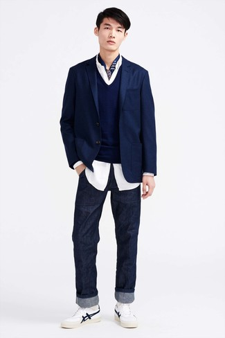 La versatilidad de un jersey de pico azul marino de Merc of London y unos vaqueros azul marino los hace prendas en las que vale la pena invertir. Tenis de cuero blancos son una opción práctica para complementar tu atuendo.