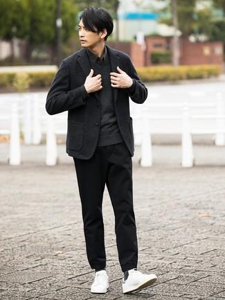 Para un atuendo que esté lleno de caracter y personalidad intenta ponerse un jersey de pico en gris oscuro y un pantalón chino negro. ¿Quieres elegir un zapato informal? Haz tenis de cuero blancos tu calzado para el día.