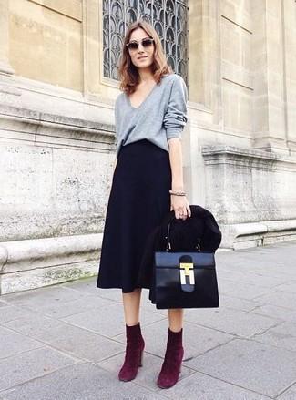 Para crear una apariencia para un almuerzo con amigos en el fin de semana elige un blazer negro y una falda campana negra. Botines de ante morado oscuro levantan al instante cualquier look simple.