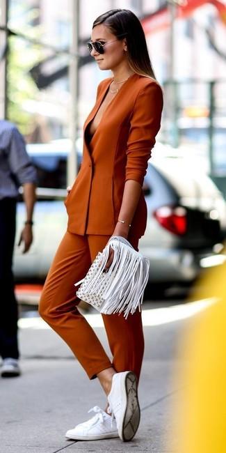 Cómo combinar un blazer naranja: Considera ponerse un blazer naranja y unos pantalones pitillo naranjas para un almuerzo en domingo con amigos. ¿Quieres elegir un zapato informal? Haz tenis de cuero blancos tu calzado para el día.