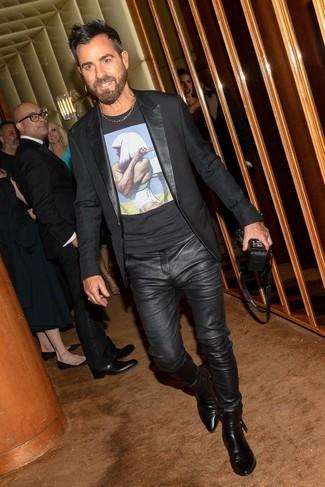 Cómo combinar: blazer negro, camiseta con cuello circular estampada negra, vaqueros de cuero negros, botines chelsea de cuero negros