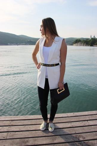 Cómo combinar: blazer sin mangas blanco, camiseta sin manga blanca, vaqueros negros, zapatillas slip-on de cuero doradas