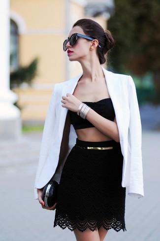 Cómo combinar: blazer blanco, top corto de encaje negro, minifalda de encaje negra, cartera sobre de cuero negra