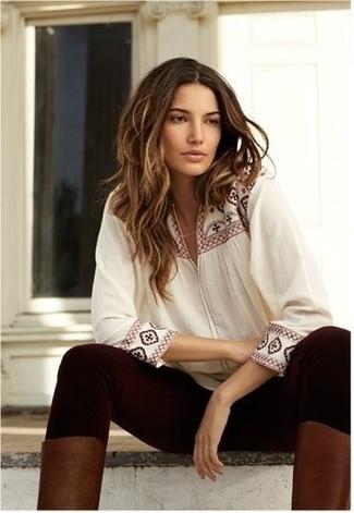 Cómo combinar: blusa campesina bordada blanca, leggings burdeos, botas de caña alta de cuero marrónes