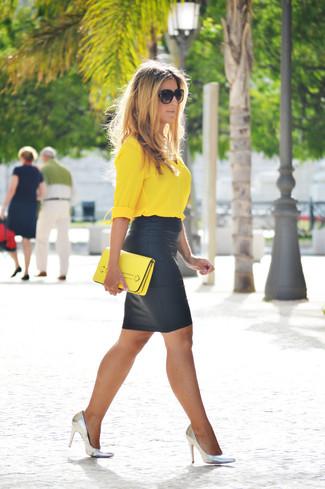 Cómo combinar: blusa de botones amarilla, falda lápiz de cuero negra, zapatos de tacón de cuero plateados, cartera sobre de cuero amarilla