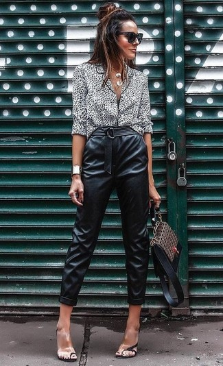 Cómo combinar: blusa de botones de leopardo en blanco y negro, pantalón de pinzas de cuero negro, sandalias de tacón de goma transparentes, bolso de hombre de cuero estampado marrón