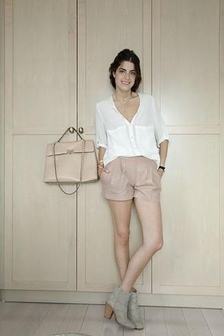 Cómo combinar: blusa de botones blanca, pantalones cortos de cuero en beige, botines de ante grises, bolso de hombre de cuero en beige