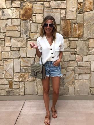 Cómo combinar: blusa de botones blanca, pantalones cortos vaqueros azules, sandalias de dedo de cuero marrónes, bolso bandolera de cuero estampado verde oliva