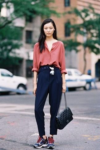 Cómo combinar: blusa de botones roja, pantalón de vestir azul marino, deportivas azul marino, bolso de hombre de cuero acolchado negro