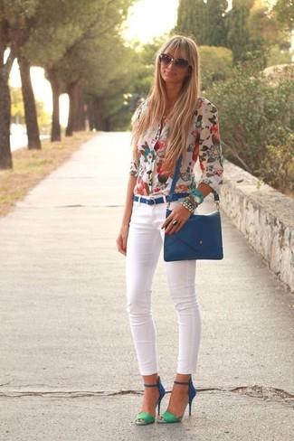 Cómo combinar: blusa de botones con print de flores blanca, vaqueros pitillo blancos, sandalias de tacón de ante azules, bolso bandolera de cuero azul