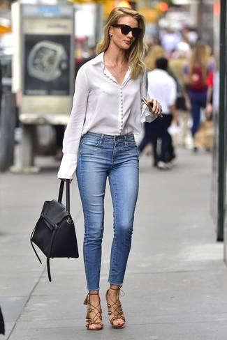 Cómo combinar: blusa de botones blanca, vaqueros pitillo azules, sandalias de tacón de ante marrónes, bolso de hombre de cuero negro