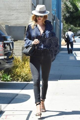 Cómo combinar: blusa de botones de estrellas azul marino, vaqueros pitillo negros, sandalias de tacón de cuero con adornos en negro y dorado, bolso bandolera de cuero acolchado negro