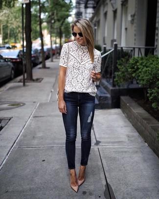 Cómo combinar: blusa de manga corta blanca, vaqueros pitillo azul marino, zapatos de tacón de cuero en beige, bolso bandolera de cuero rosado
