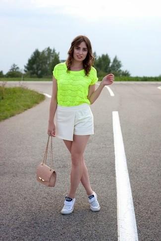 Cómo combinar: blusa de manga corta de encaje en amarillo verdoso, pantalones cortos en beige, tenis blancos, bolso bandolera de cuero rosado