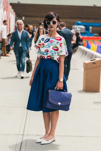 Cómo combinar: blusa de manga corta estampada blanca, falda campana azul marino, bailarinas de cuero blancas, bolso de hombre de cuero azul