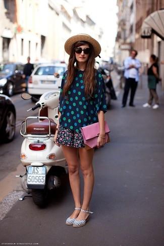 Cómo combinar: blusa de manga corta a lunares en azul marino y verde, falda skater con print de flores negra, sandalias de lona de rayas horizontales grises, cartera sobre de cuero rosada