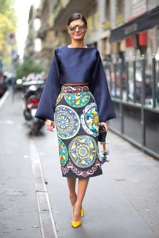 Cómo combinar: blusa de manga larga de satén azul marino, falda midi estampada azul marino, zapatos de tacón de cuero amarillos, gafas de sol grises