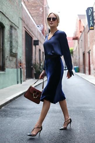 Look de moda: Blusa de manga larga de satén azul marino, Falda midi de terciopelo azul marino, Zapatos de tacón de cuero negros, Bolso de hombre de cuero burdeos