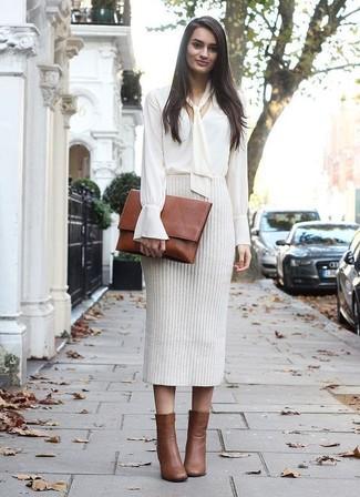 Cómo combinar: blusa de manga larga blanca, falda lápiz de punto en beige, botines de cuero marrónes, cartera sobre de cuero marrón