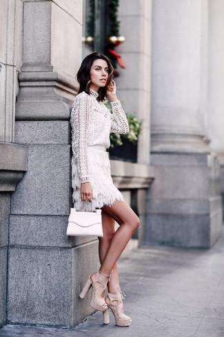 Cómo combinar: blusa de manga larga con ojete blanca, minifalda сon flecos blanca, sandalias de tacón de ante en beige, cartera sobre de cuero blanca