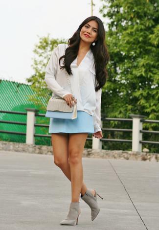 Cómo combinar una minifalda celeste: Elige una blusa de manga larga de seda blanca y una minifalda celeste para una apariencia fácil de vestir para todos los días. Botines de ante con recorte grises son una opción buena para completar este atuendo.