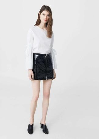 Cómo combinar una minifalda de cuero negra en clima caliente: Utiliza una blusa de manga larga blanca y una minifalda de cuero negra para un almuerzo en domingo con amigos. Chinelas de cuero negras son una forma sencilla de mejorar tu look.