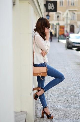 Cómo combinar: blusa de manga larga de seda blanca, vaqueros pitillo desgastados azules, sandalias de tacón de cuero negras, bolso bandolera de cuero marrón claro