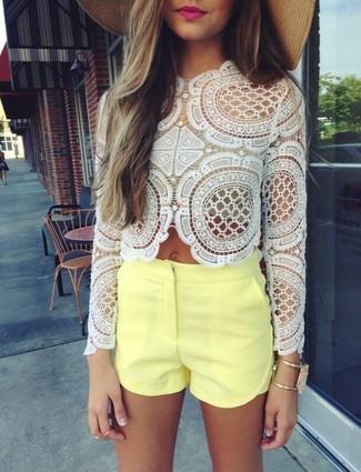 Utiliza una blusa de manga larga de encaje blanca y unos pantalones cortos naranjas y te verás como todo un bombón.