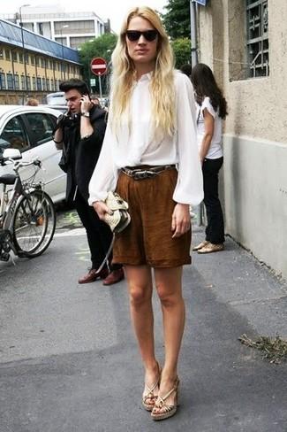 Cómo combinar: blusa de manga larga de seda blanca, bermudas marrónes, sandalias con cuña de cuero en beige