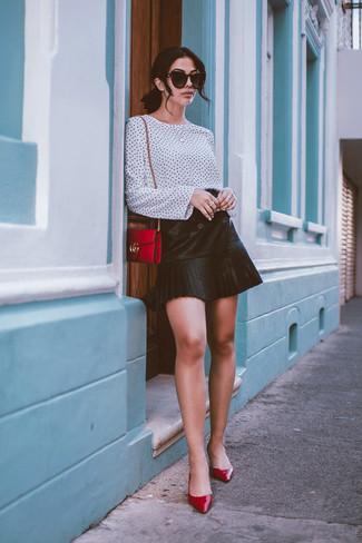 Cómo combinar: blusa de manga larga a lunares en blanco y negro, minifalda de cuero plisada negra, zapatos de tacón de cuero rojos, bolso bandolera de cuero rojo