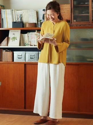 Cómo combinar: blusa de manga larga mostaza, pantalones anchos blancos, mocasín de cuero marrónes
