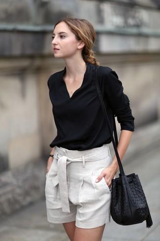 Cómo combinar: blusa de manga larga negra, pantalones cortos de lino en beige, mochila con cordón de cuero negra
