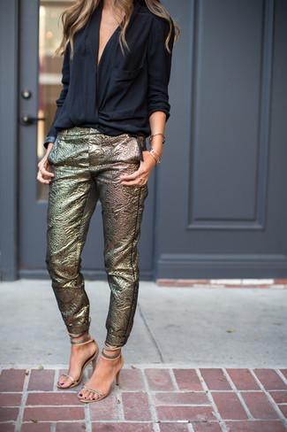 Cómo combinar: blusa de manga larga negra, pantalones pitillo dorados, sandalias de tacón de cuero plateadas