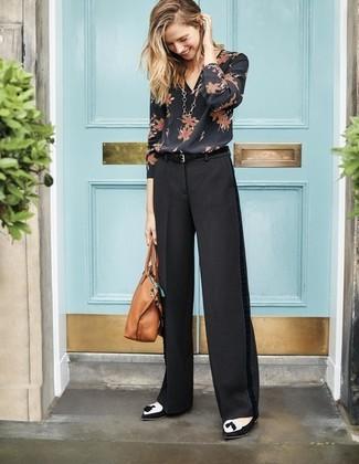 Cómo combinar: blusa de manga larga con print de flores negra, pantalones anchos negros, mocasín con borlas de ante en negro y blanco, bolsa tote de cuero marrón claro