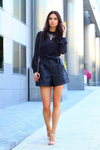 Cómo combinar: blusa de manga larga de gasa negra, pantalones cortos de cuero negros, sandalias de tacón de cuero plateadas, bolso bandolera de cuero negro