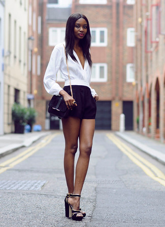 Cómo combinar: blusa de manga larga blanca, pantalones cortos negros, sandalias de tacón de ante negras, bolso bandolera de ante negro