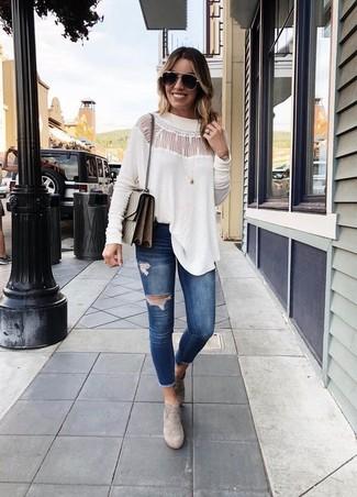 Cómo combinar: blusa de manga larga de encaje blanca, vaqueros pitillo desgastados azul marino, botines de ante grises, bolso bandolera de cuero marrón
