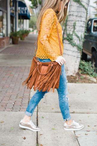 Empareja una blusa de manga larga de encaje amarilla junto a unos vaqueros pitillo desgastados azules para lidiar sin esfuerzo con lo que sea que te traiga el día. Tenis de cuero plateados añadirán interés a un estilo clásico.